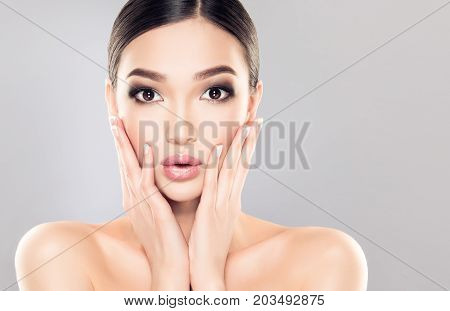 Beautiful young asian woman with Clean Fresh Skin on face .Oriental girl Facial  treatment .Cosmetology , beauty  and spa . Amazed and impressed Asian girl. Expressive emotions on face  Asian woman .