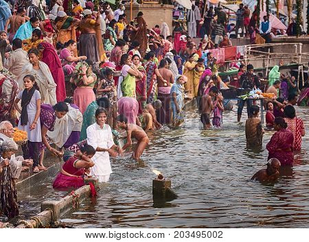 VARANASI, INDIA - NOVEMBER 15, 2016: On the morning after the Dev Diwali festival, an anonymous young woman in white bathes in the holy waters of the Ganges River amid a crowd on steps of a ghat in Varanasi.
