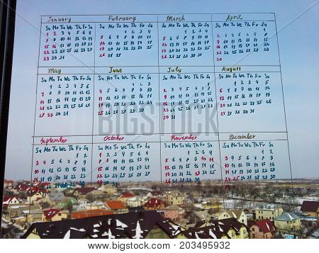 Calendar written on the window glass with a beautiful view from the window in the background