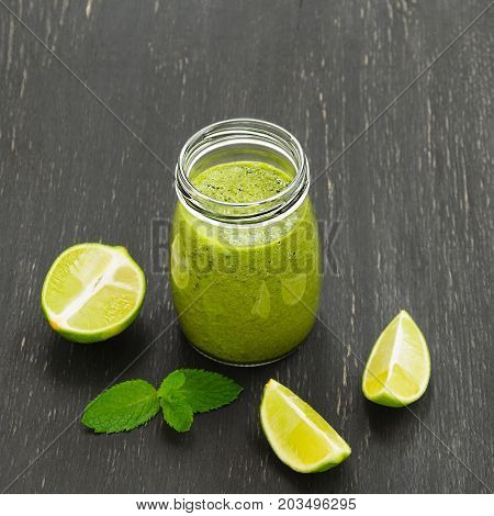 Green homemade smoothies with lime on black background. Selective focus. Diet Detox Clean Eating or Vegetarian concept. Green smoothies of banana spinach lime kale celery mint
