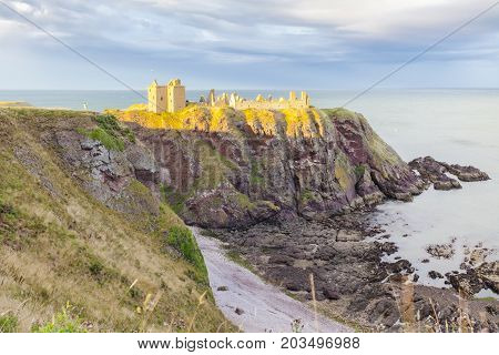 Stonehaven - august 2014: a photographer is taking a picture at sunset at the Dunottar Caslte It is located on a peninsula overlooking the North Sea