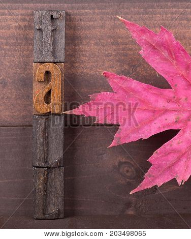 Wood letters spelling fall with autumn maple leaf on a wooden background