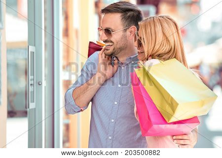 Sale consumerism and people concept - happy couple with shopping bags looking at shop window in city.