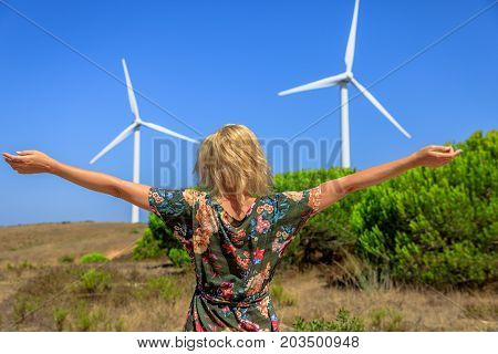 A blond caucasian woman with open arms enjoying in front of wind turbines rotating in Sagres, Algarve, Portugal. Alternative energy, renewable energy and environmental sustainability concept.