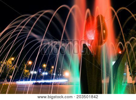 A close-up picture of beautiful illuminated city fountain A Tulip Flower at fall evening in Pokrov town in Ukraine, 2017