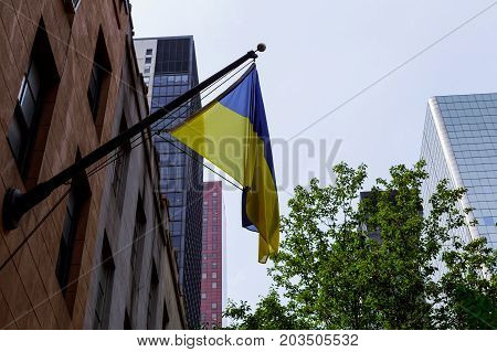 Ukrainian flag on the building Flag of Ukraine with a black mourning ribbon.
