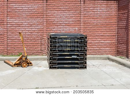 A pallet Jack next to a stack of metal pallets.