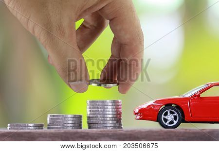 Hand of businessmen are silver coin placed on money graph in concept of saving and insurance for vehicles.