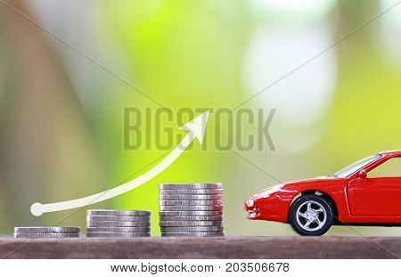 Concept of investing in automotive businessCoin pile graph and red toy car.
