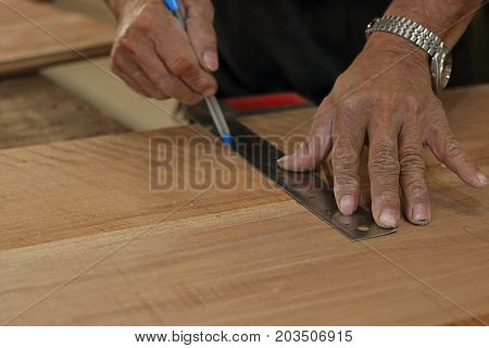Selective focus and shallow depth of field. Ruler taking measurement on a wooden plank with hand of senior carpenter in workshop