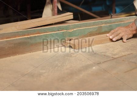 Selective focus and shallow depth of field. A piece of wood is being shaved on a router table by hands of carpenter in carpentry workshop.