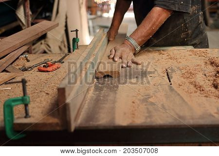 Piece of wooden board is being shaved on a router table by hands of senior carpenter in carpentry workshop.Selective focus and shallow depth of field.