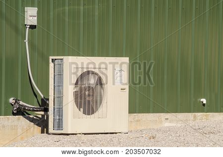 An HVAC unit isolated against the building.