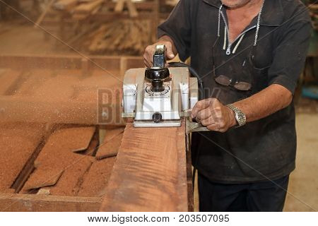 Electric planer shaving a piece of wooden board with hands of senior carpenter in carpentry workshop. Selective focus and shallow depth of field.
