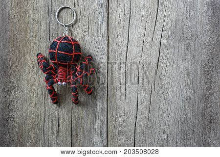 Key chain spider on old wooden background and have copy space for design in your work backdrop.