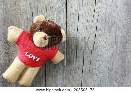 Teddy Bear is placed on old brown wood floor and have copy space to your input idea in work.
