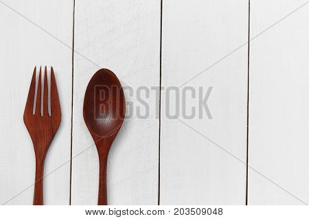 Wooden spoon and wooden fork on white wooden floor background for design in your work.