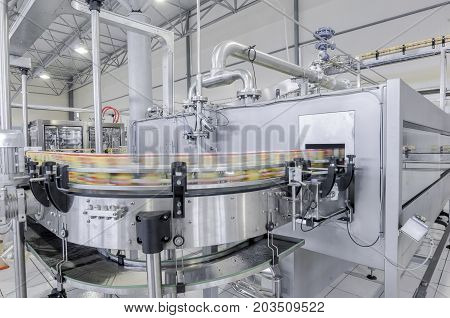 conveyor belt in motion at production and bottling of drinks in tin cans. production and bottling of drinks in tin cans