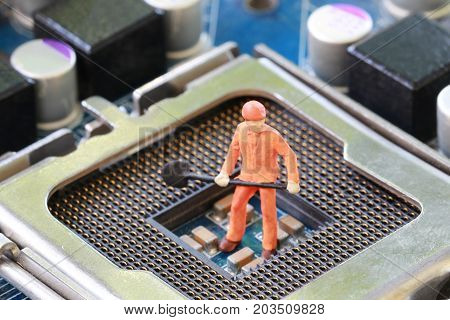 Idea of a worker is miners are digging for ore on computer mainboard in concept of doing business and digital currency.