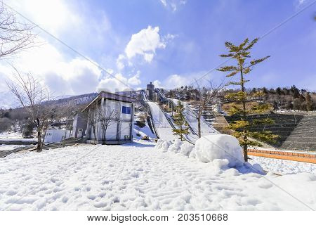 Ski jump area or ski springboards against with snow on the mountain and blue sky and clouds background in Hakuba Nagano Japan.