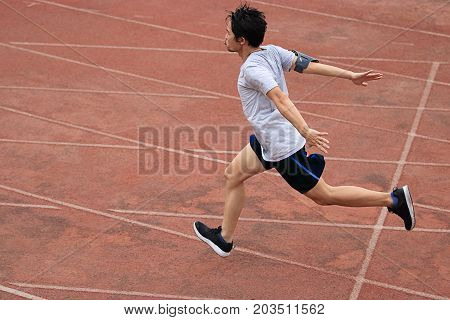 Athletic Asian runner sprinter crossing the finish line.