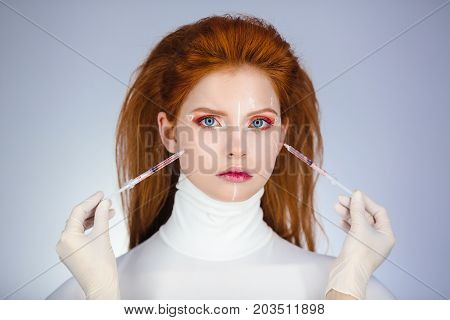 Beautiful Woman before Plastic Surgery Operation Cosmetology. Beauty Portrait Fashion Concept. Treatment with botox or hyaluronic collagen injection. Young red hair girl holding syringes in hands with correction mark for plastic surgery on her sad face wi