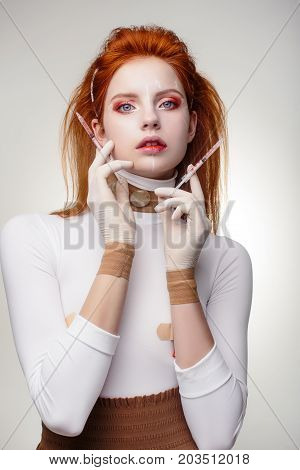 Beautiful Woman before Plastic Surgery Operation Cosmetology. Beauty Portrait Fashion Concept. Young red hair girl holding syringes in hands with correction mark for plastic surgery on her face