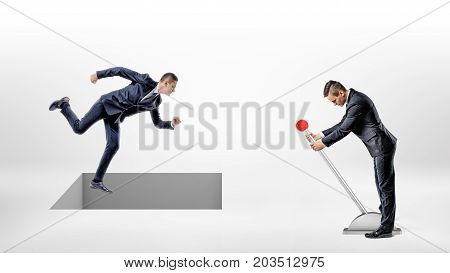 A businessman runs on white ground while a square hole controlled by a man on a lever opens right under his feet. Finance trap. Credit rate robbery. Corporate relations.