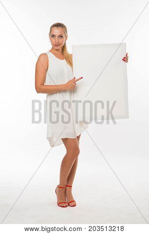 Young sexy woman portrait of a confident businesswoman showing presentation, pointing placard gray background. Ideal for banners, registration forms, presentation, landings, presenting concept.