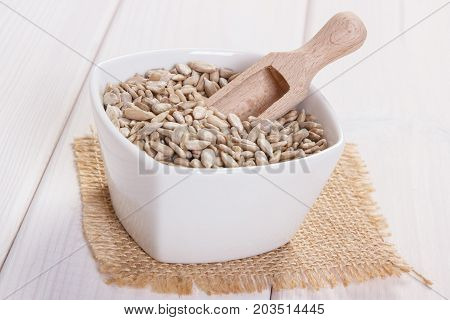 White bowl with sunflower seeds containing zinc and dietary fiber on white boards natural sources of minerals healthy lifestyle and nutrition