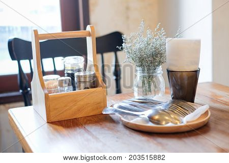 Beautiful houseplant in flowerpot tissue in black box garnish (pepper toothpick sauce) in wooden box and spoon/fork set on wooden table and black chair for food background - interiors concept.