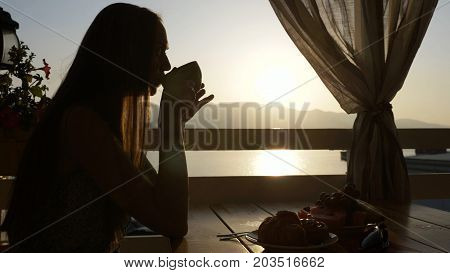 Silhouette of young beautiful woman sits in a cafe with panoramic views of sea bay and drinking tea or coffee, profile view with beautiful sunrise light.