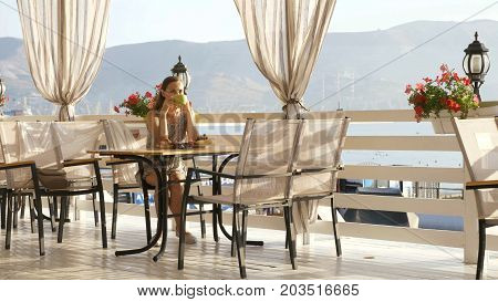 Young pretty woman in dress sits in a cafe beholding beautiful panoramic views of sea bay. Morning with warm sunrise light and cup of coffee or tea