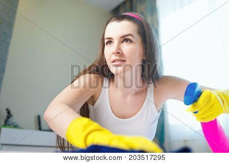 Young Woman Wiping The Dust On The Table.a House Cleaner Cleans Up Dust.girl Smiling And Doing House