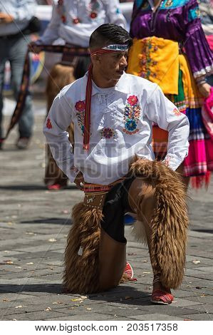 June 17 2017 Pujili Ecuador: indigenous kichwa man in traditional clothing wearing chaps kneeling at the Inti Raymi parade