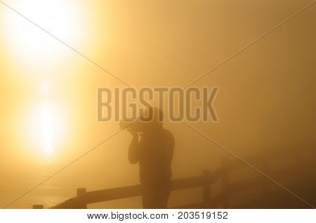 Silhoutte of a photographer shooting a sunrise in the West Thumb Area in Yellowstone National Park.