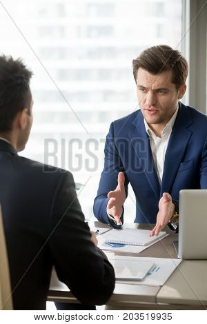 Serious successful businessman discussing company results with financial director, planning personnel policy with human resources manager, explaining details of perspective project to business partner