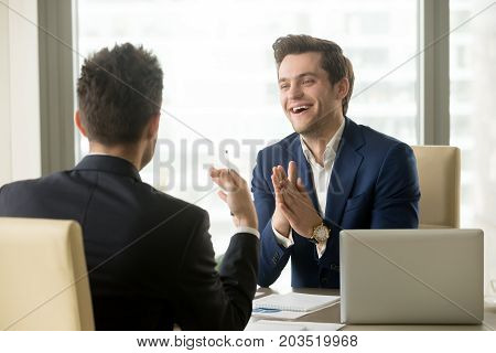 Happy smiling businessman having pleasant conversation with business partner on meeting in office. Two colleagues in business suits discussing interesting project details, sharing impressions of work