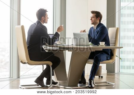 Two handsome businessmen sitting in comfortable chairs at desk with laptops in meeting room. CEO making important negotiation about companies partnership or corporate merger. Financiers planning deal