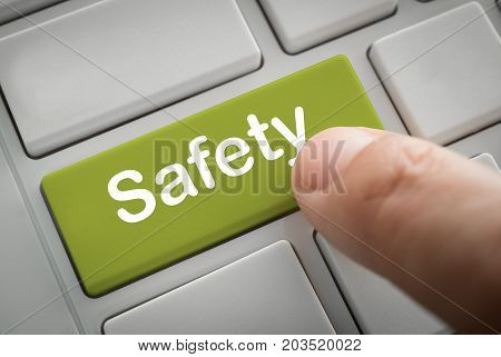 Safety Concept. Businessman fingers press in safety button of a computer keyboard.