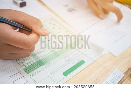 Asian Students holding pencil in hand doing multiple-choice quizzes or testing exams answer sheets exercises on old wood table In secondary school college university classroom in education concept