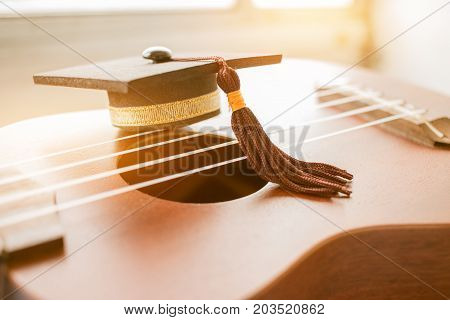 Graduation cap Put on ukulele a small instrument. The ukulele is member of lute family of instruments with nylon stringed usually played with bare thumb or fingertips. Concept of Music Education.