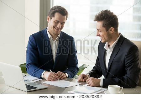 Happy smiling businessman signing contract with satisfied business partner, accepting terms of agreement, making good deal with perspective company. Investor approving financing of interesting project