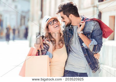 Saleconsumerism and people concept.Happy beautiful young couple holding shopping bags and smilling.