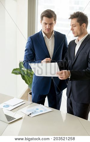 Businessman showing documents with financial statistics to business partner, explaining prospects of project with charts, convincing client to invest in company while presenting growth calculations