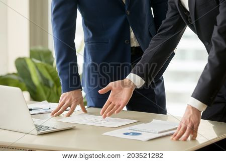 Businessman pointing on apartments drawings lying on desk during construction project presentation. Architect or realtor discussing house plan with client. Internal space planning. Close up image