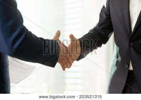 Close up photo of businessmen hands stretched out for handshaking. Business partners welcoming each other before or after contract negotiation, reaching consensus in determining terms of agreement