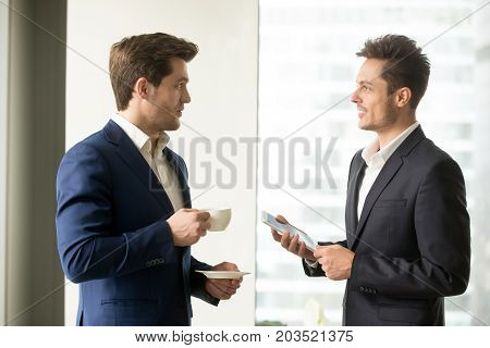 Handsome businessman with coffee cup in hands talking with colleague. Male business partners discussing perspective ideas using digital tablet during coffee break. CEO planning day with male secretary