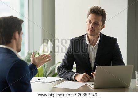 Candid millennial businessman listening offer of business partner, discussing plans with colleague, communication with client while sitting at office desk. Employer making interview with applicant