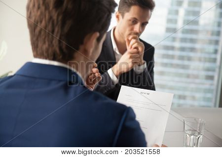 Back view of hiring manager reading resume focus on document, worried job candidate waiting for decision on background. Company recruiter doubting in applicants qualifications, conducting interview